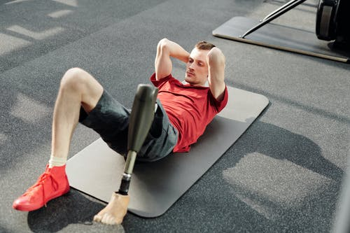 Man in Red Tank Top Lying on Gray Yoga Mat