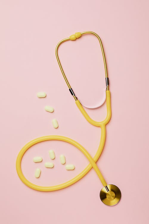 Yellow Stethoscope And Tablets On Pink Background