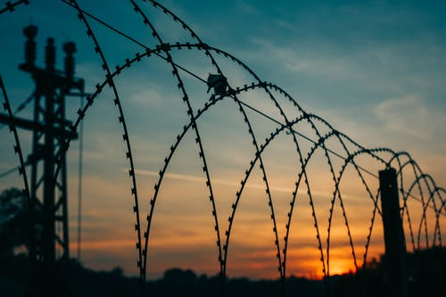 Silhouette of Wire Fence On Mountain During Sunset