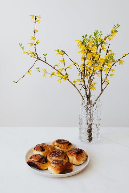 Baked Breads on White Plate Near Yellow Flowers