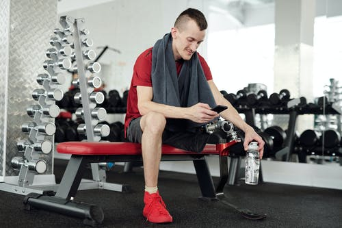 Man in Red and Black Polo Shirt and Black Pants Sitting on Red and Black Exercise Bench