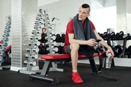 Man in Red Shirt and Black Shorts Sitting on Red and Black Chair