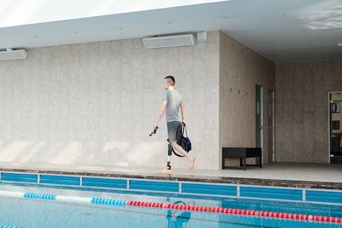 プールのそばを歩く義足を持つ男