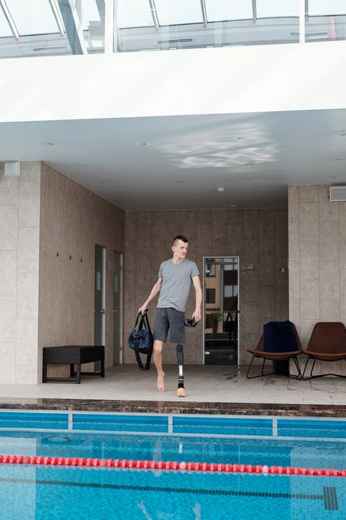 Man with Prosthetic Leg Walking by Swimming Pool