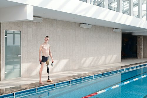 Man with Prosthetic Leg Standing by Swimming Pool