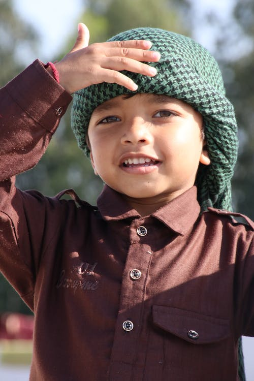 Boy Wearing A Brown Button Up Shirt And Turban