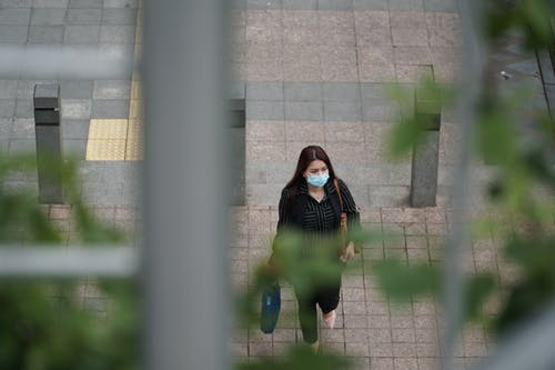 Unrecognizable lady walking on pavement during COVID 19 pandemic