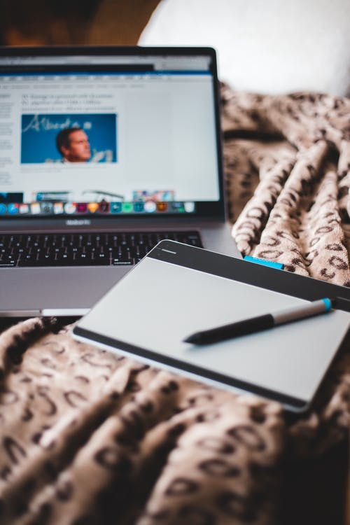 From above of open netbook with picture on screen near notebook with empty sheet of paper with pen on crumpled plaid on bed with pillow at home
