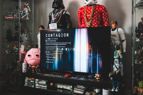 Desktop computer with creative video game on screen near assorted toy superheros on glass shelves in modern style apartment