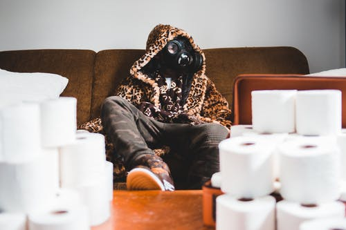 Unrecognizable trendy man in respirator near pile of toilet paper