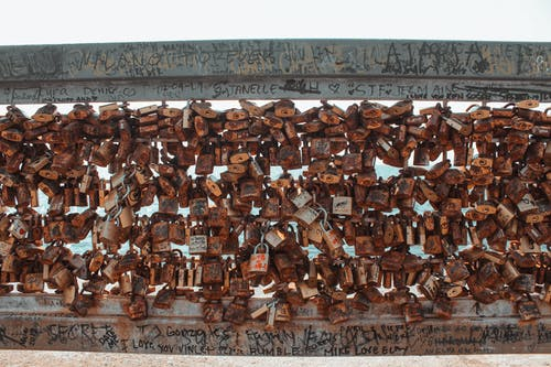 Many old rusty locks hanging on cement wall in city