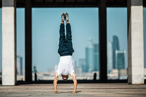 Man in Blue Denim Jacket and White Shorts In Handstand Position