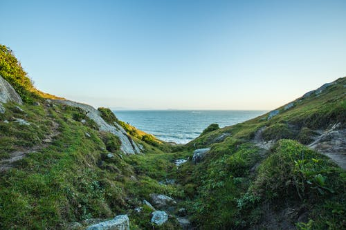 Green Grass Covered Hill by the Sea Under Blue Sky