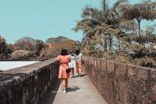 Unrecognizable women walking on old pathway near trees in park