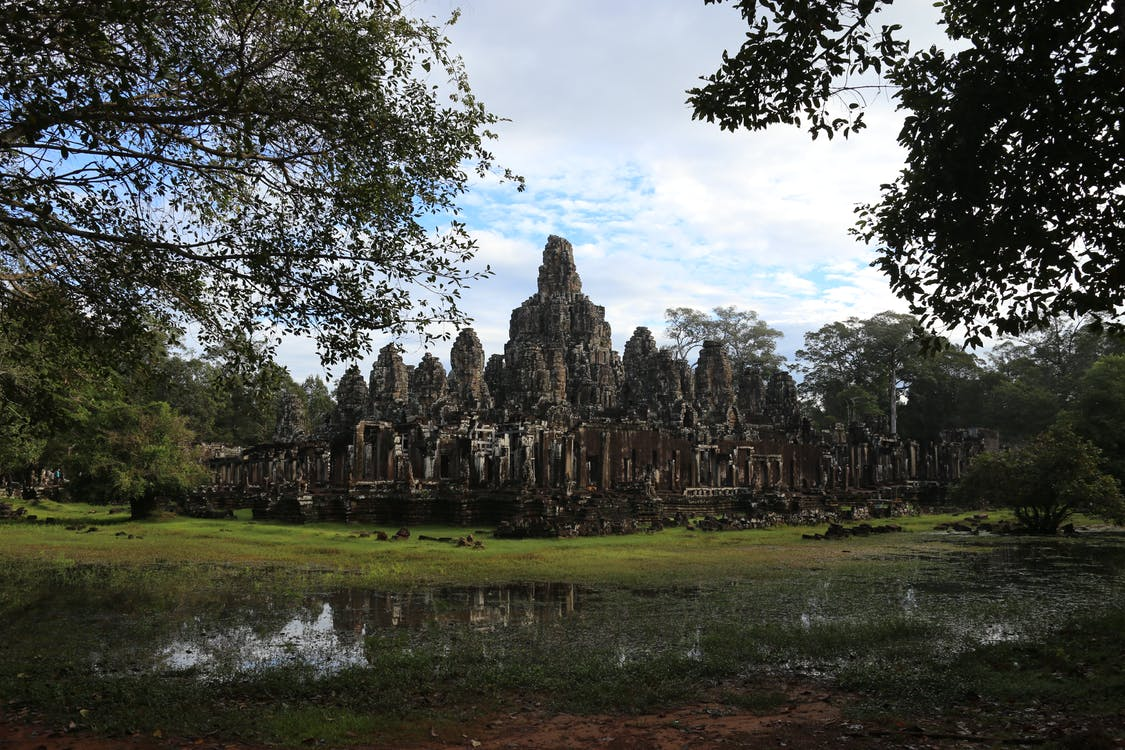 Scenery view of aged church complex exterior on green field near rippled pond and growing trees under cloudy sky in Cambodia