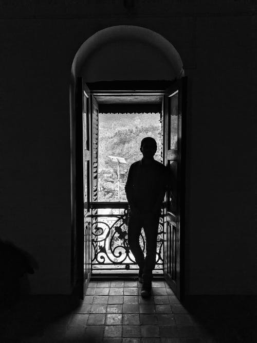 Black and white full body back view of anonymous male admiring trees while standing leaned on one leg near ornamental metal fence on tiled floor in building