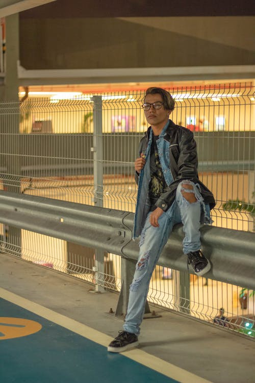 Trendy fit ethnic man sitting on concrete fence indoors