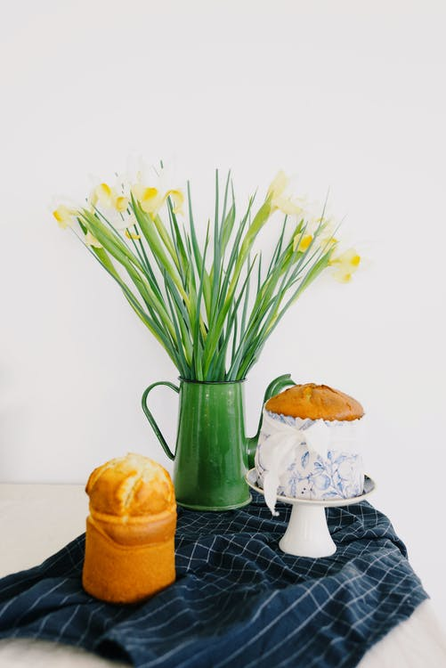 Metal pitcher with flower bouquet with gentle petals and long leaves put on towel near yummy panettones with golden surface for Easter holiday