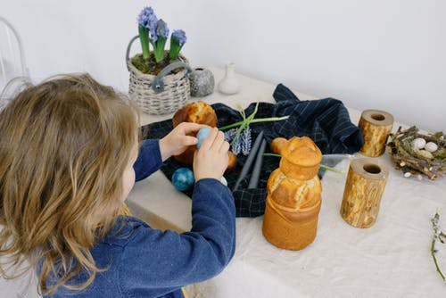 Little Girl Holding an Egg over a Table With Easter Decorations