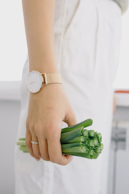 Unrecognizable cook in white clothes and wristwatch standing near table and holding healthy cut salad before cooking lunch in contemporary studio
