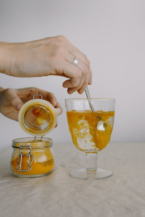 Crop hands adding turmeric in glass of hot water in morning