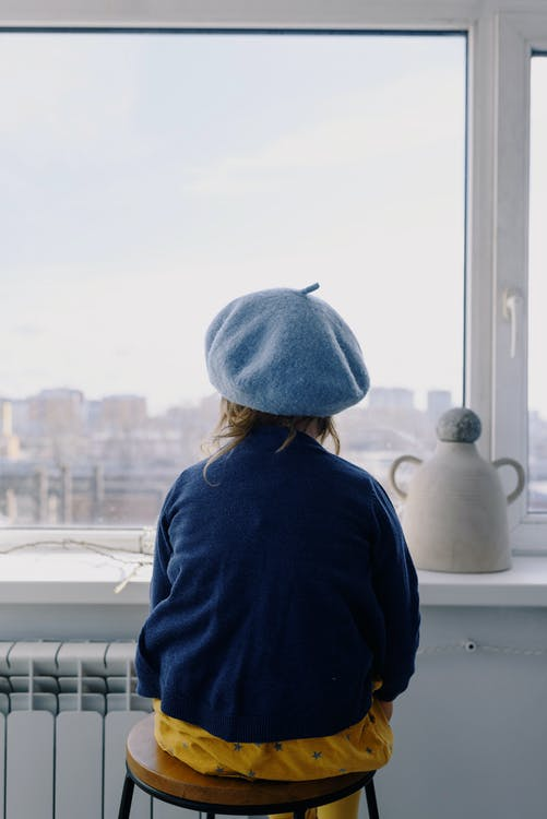 Adorable little girl in beret looking out window