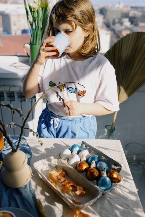 Little Girl Drinking From a Mug