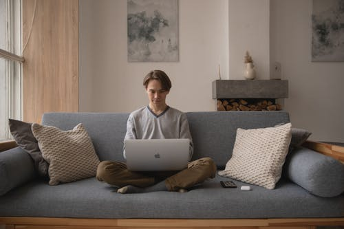 Man Sitting On Couch With a Laptop