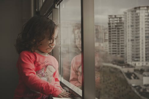 Photo Of Girl Looking Out The Window