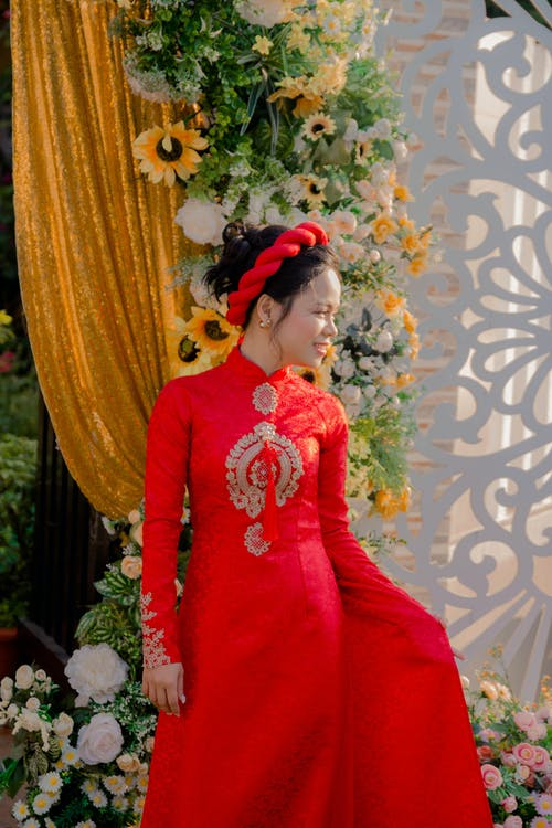 Positive Asian female in national colorful dress and accessory on head looking away while standing near ornamental fence and flowers during celebration
