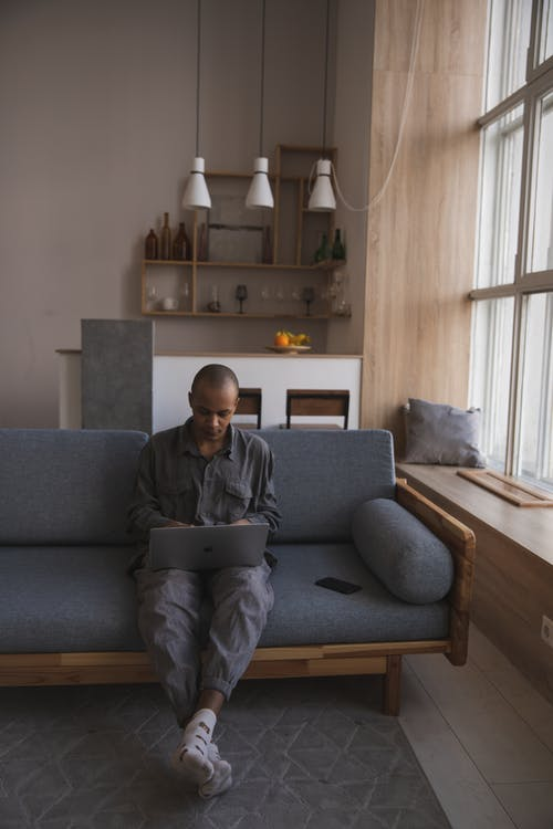 Focused young ethnic man with laptop in living room