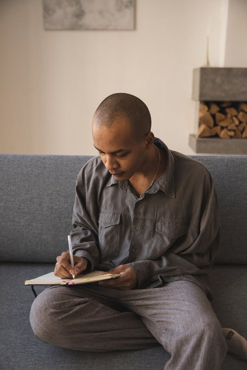 Thoughtful young ethnic man writing on notebook at home