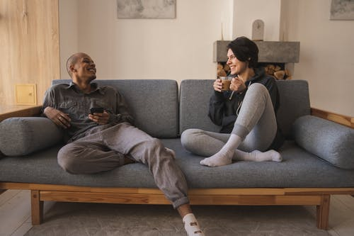 Cheerful young diverse couple relaxing on couch at home