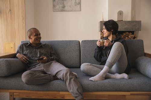Happy young multiracial couple taking on sofa at home