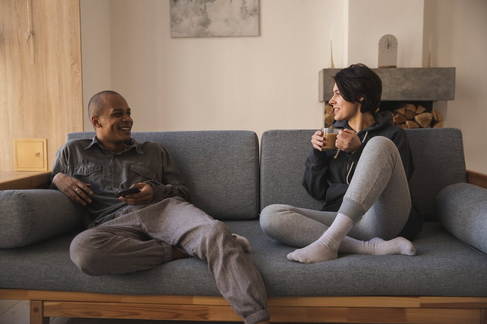 Happy couple taking on sofa at home. | Photo: Pexels