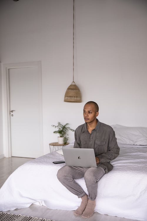 Photo Of Man Sitting On A Bed