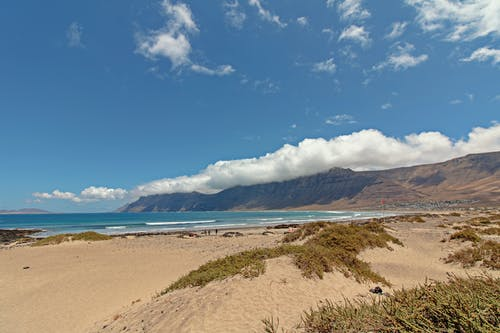 Kostnadsfri bild av bergen, dagsljus, gräs, hav
