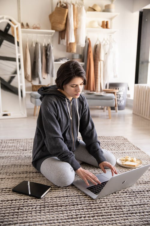Serious young woman sitting on floor with laptop at home