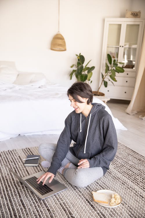 Young woman using laptop on floor