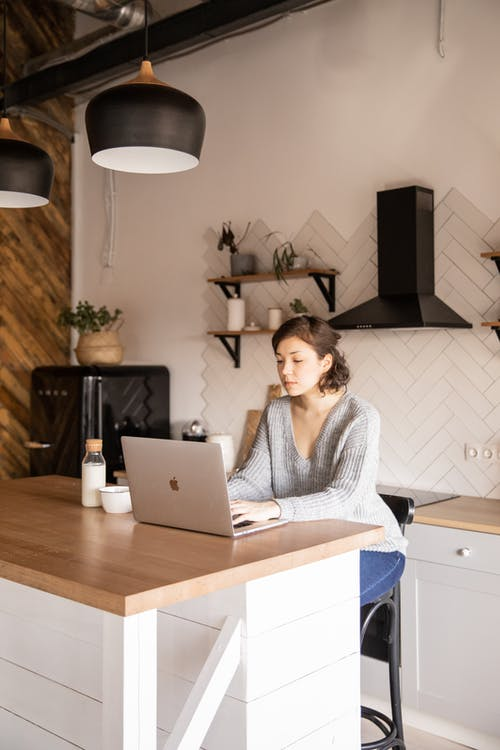 Young female freelancer using laptop in kitchen