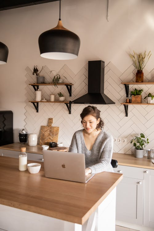 Focused woman in casual outfit sitting at counter with milk bottle in modern kitchen and browsing netbook while working on remote project at home