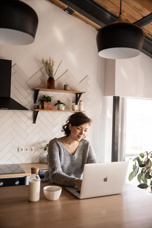 Cheerful young woman using laptop in kitchen