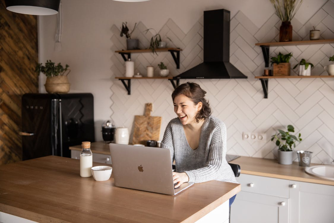 Happy woman using laptop in kitchen