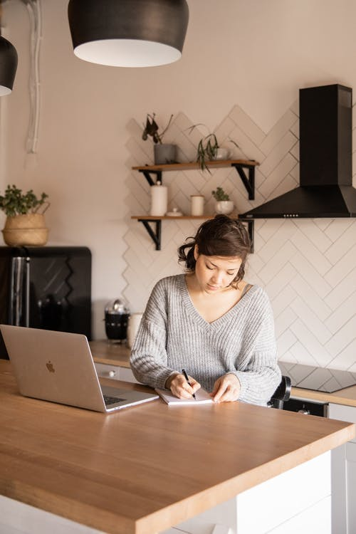 Young female freelancer with laptop and notepad in kitchen