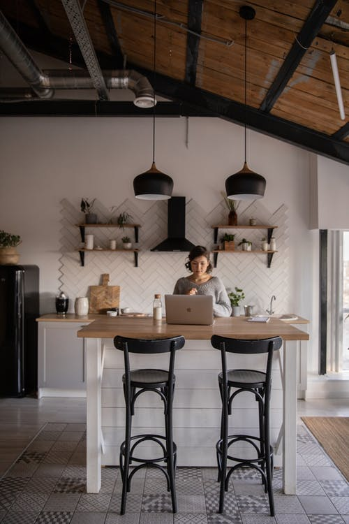 Young woman with laptop in modern kitchen interior