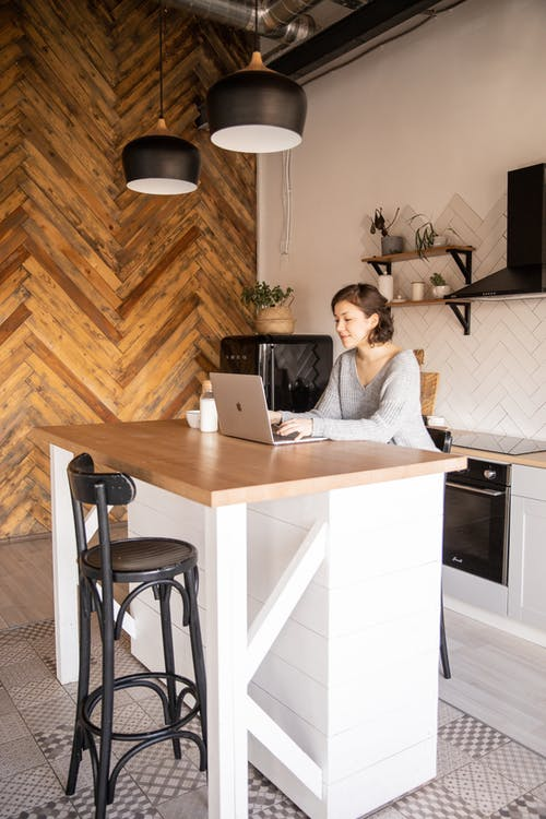 Positive young woman with laptop in modern kitchen