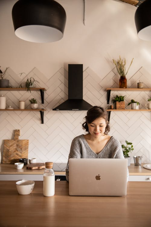 Young female student in gray sweater sitting at wooden desk with laptop and bottle of milk near white bowl during distance education at home