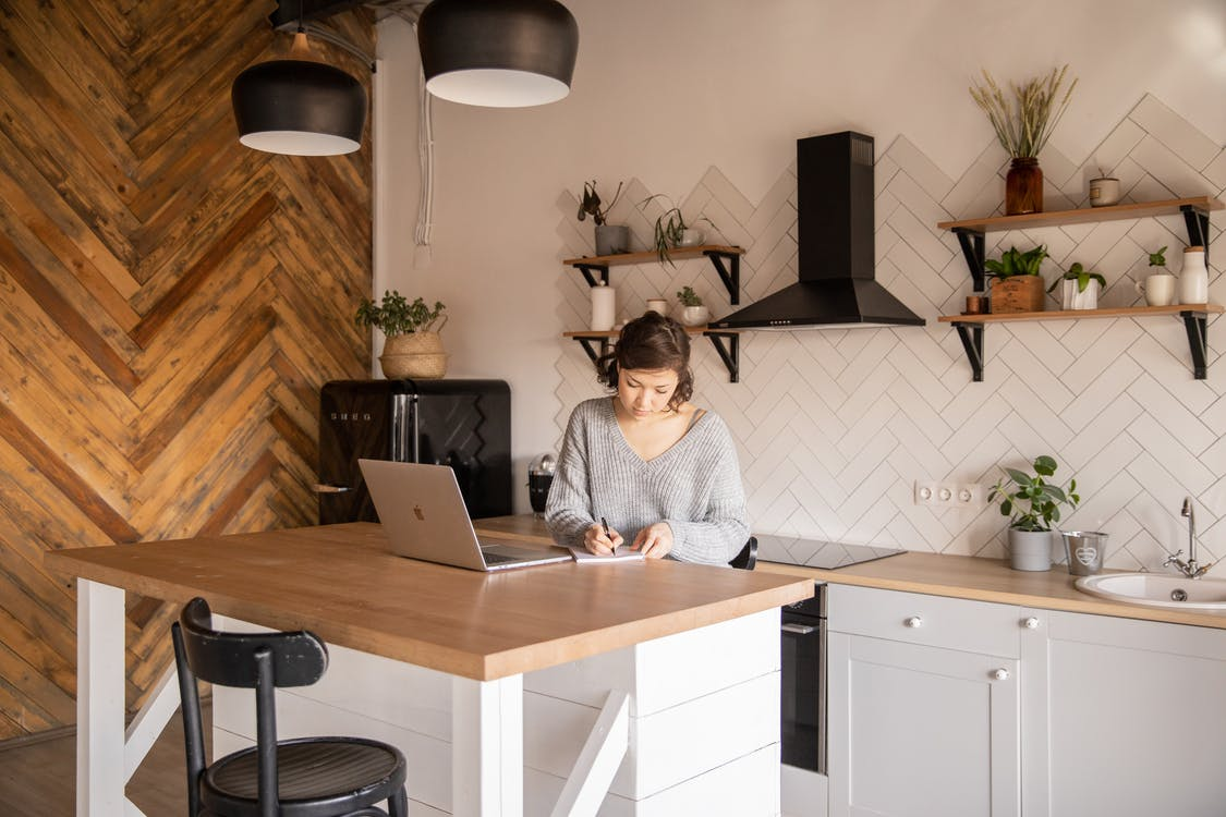 Busy female freelancer with laptop taking notes in kitchen
