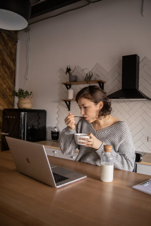 Young woman using laptop during breakfast