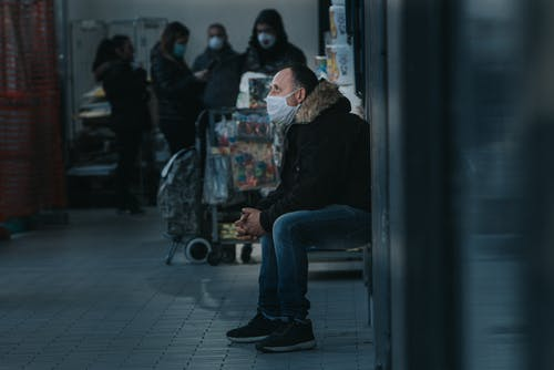 Side view of male in warm clothes and mask sitting in public place